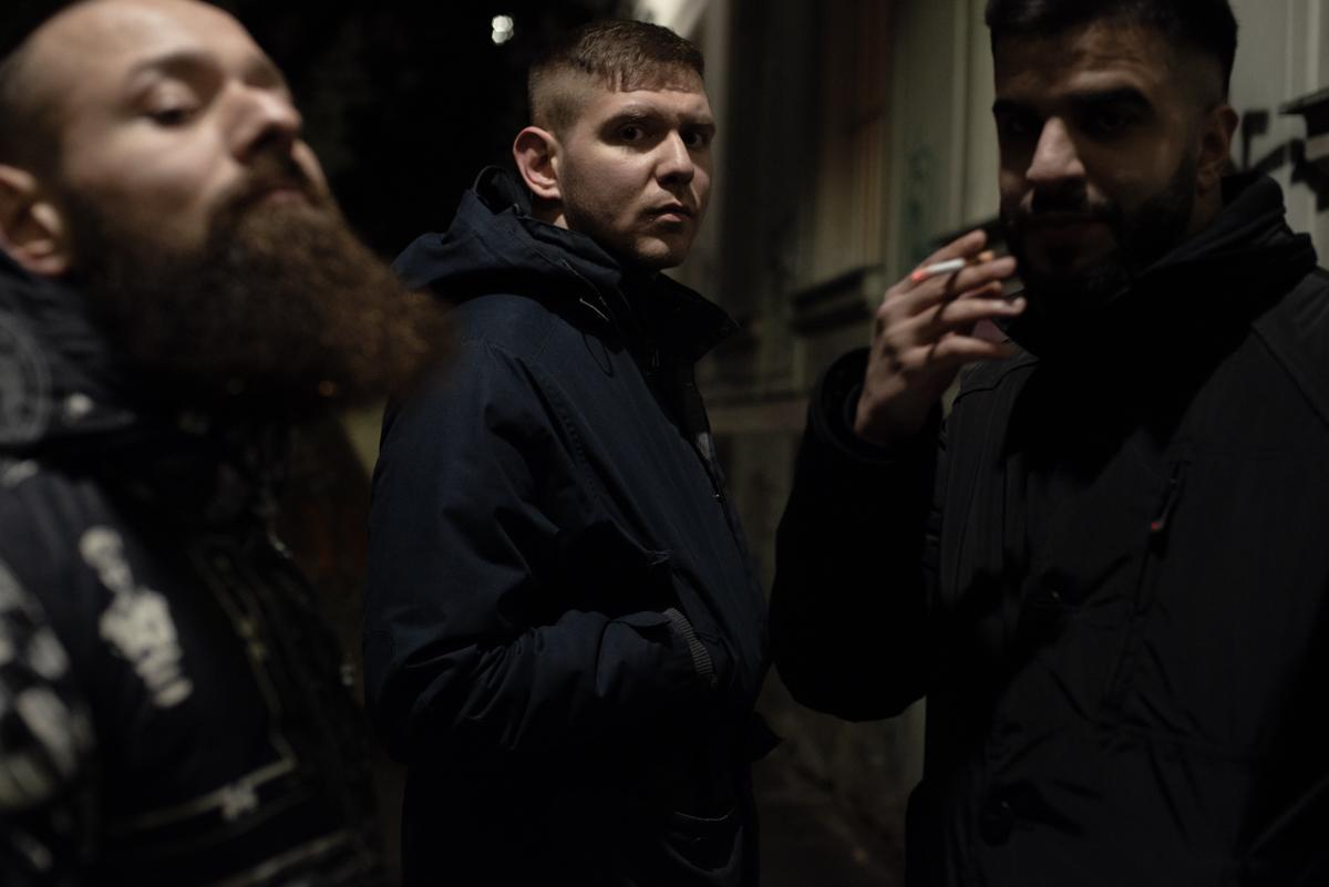 3 Männer vor einer Graffitiwand